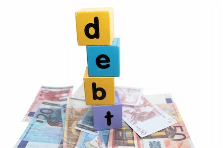 assorted childrens toy letter building blocks against a white background on money that spell debt Stock Photo - Budget Royalty-Free & Subscription, Code: 400-05241316