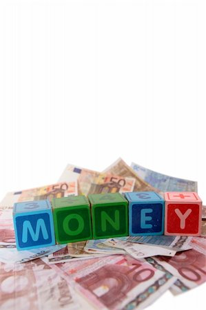 assorted childrens toy letter building blocks against a white background on money that spell money with copy space Stock Photo - Budget Royalty-Free & Subscription, Code: 400-05241317