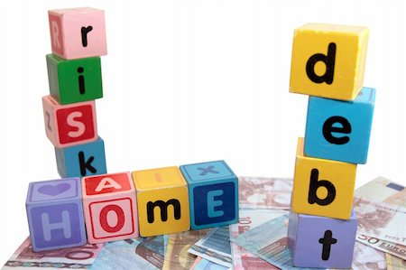 assorted childrens toy letter building blocks against a white background on money that spell home debt risk Stock Photo - Budget Royalty-Free & Subscription, Code: 400-05241318