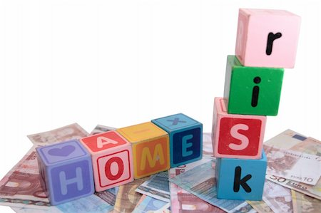 assorted childrens toy letter building blocks against a white background on money that spell home risk Stock Photo - Budget Royalty-Free & Subscription, Code: 400-05241319