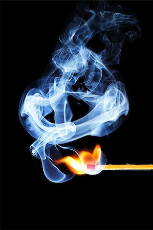 one match is igniting in front of black background with blue smoke Stock Photo - Budget Royalty-Free & Subscription, Code: 400-05241990