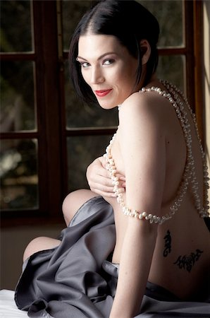 Sexy naked young caucasian adult woman with red lips, short black hair and a pierced eyebrow, covered in a dark satin sheet and sitting on a bed and wearing a string of pearls Stock Photo - Budget Royalty-Free & Subscription, Code: 400-05276286