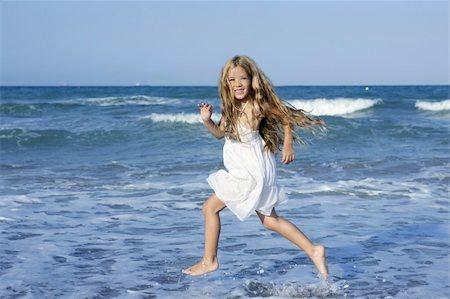 Little girl running beach shore splashing water in blue sea Stock Photo - Budget Royalty-Free & Subscription, Code: 400-05273743