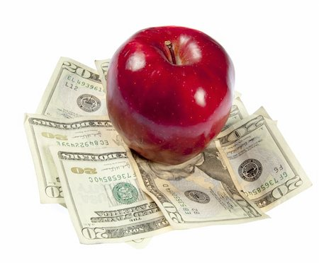 education loan - A red apple sits on top of a pile of $20 bills to illustrate the cost of education, food, or health care.  Studio shot on a white background. Stock Photo - Budget Royalty-Free & Subscription, Code: 400-05280570