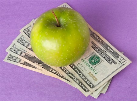 education loan - A green apple sits on top of a pile of $20 bills to illustrate the cost of education, food, or health care. Stock Photo - Budget Royalty-Free & Subscription, Code: 400-05280674