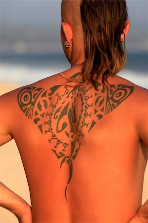 The young man with a beautiful tattoo on a coast of ocean Stock Photo - Budget Royalty-Free & Subscription, Code: 400-05295908