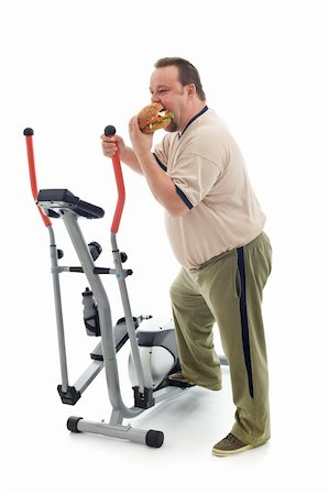 fat man exercising - Overweight man eating a large hamburger standing by an exercising device - fittness fail concept isolated Stock Photo - Budget Royalty-Free & Subscription, Code: 400-05309444