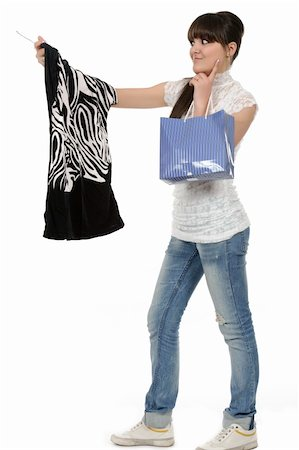 young woman shopping. In her hand is a blouse on a hanger and a bag Stock Photo - Budget Royalty-Free & Subscription, Code: 400-05310194