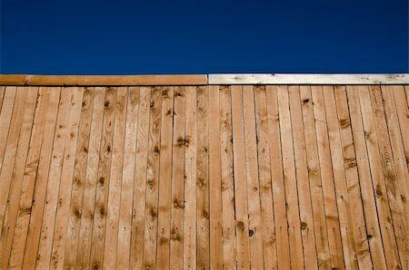 Image of a wooden fence shot from a low angle looking slightly up with blue sky Stock Photo - Budget Royalty-Free & Subscription, Code: 400-05322119