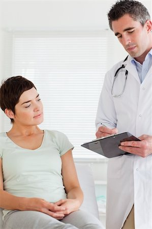 Male Doctor and female patient looking at a chart in a room Stock Photo - Budget Royalty-Free & Subscription, Code: 400-05357165