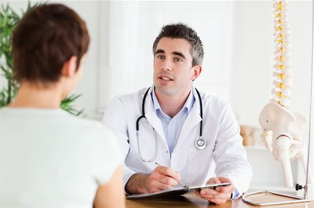 Male Doctor writing something down while patient is talking in a room Stock Photo - Budget Royalty-Free & Subscription, Code: 400-05357277