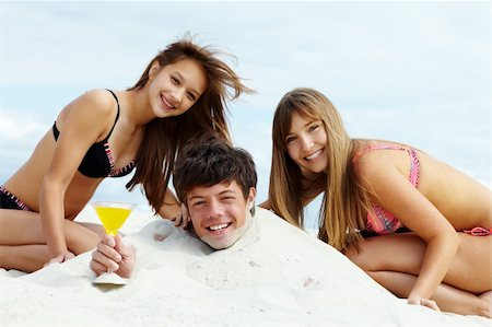 pressmaster (artist) - Two girls in bikini and happy guy with cocktail having fun on sandy beach Stock Photo - Budget Royalty-Free & Subscription, Code: 400-05358827