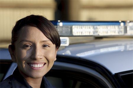 female police officer happy - a happy female police officer standing next to her patrol unit. Stock Photo - Budget Royalty-Free & Subscription, Code: 400-05360785