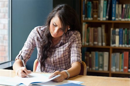 Young student writing in a library Stock Photo - Budget Royalty-Free & Subscription, Code: 400-05669939