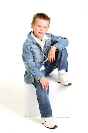 young attractive boy wearing a blue jean jacket sitting and smiling Stock Photo - Budget Royalty-Free & Subscription, Code: 400-05663603