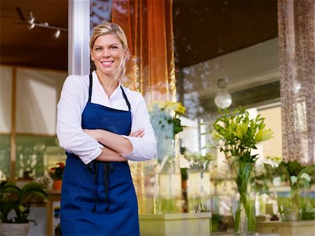 Portrait of beautiful caucasian girl self-employed in flower shop, smiling and looking at camera. Horizontal shape, waist up Stock Photo - Budget Royalty-Free & Subscription, Code: 400-05674607