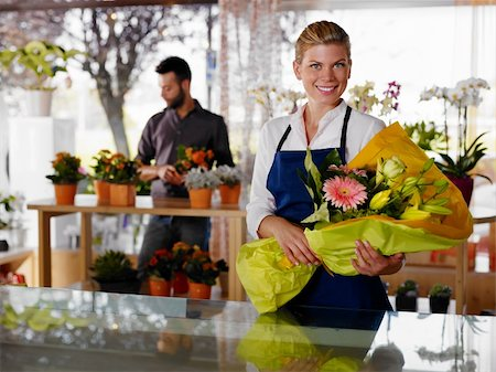 Female sales assistant working as florist and holding bouquet with customer in background. Horizontal shape, waist up Stock Photo - Budget Royalty-Free & Subscription, Code: 400-05674622