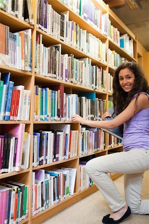 Portrait of a smiling female student choosing a book in a library Stock Photo - Budget Royalty-Free & Subscription, Code: 400-05678093