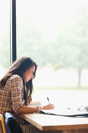 Portrait of a serious young student writing an essay in a library Stock Photo - Budget Royalty-Free & Subscription, Code: 400-05670300