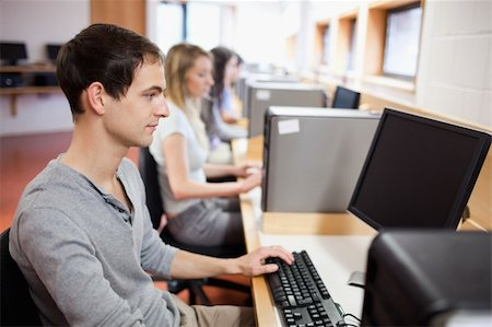 Smiling male student posing with a computer in an IT room Stock Photo - Budget Royalty-Free & Subscription, Code: 400-05684121
