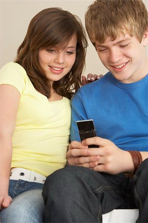 pre-teen boy models - Teenage Couple Reading Text Message Stock Photo - Budget Royalty-Free & Subscription, Code: 400-05697207