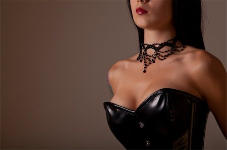Close-up shot of busty woman in black corset, studio shot on creamy background Stock Photo - Budget Royalty-Free & Subscription, Code: 400-05693028