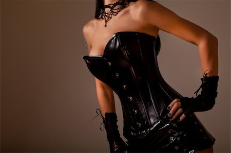 Close-up shot of busty woman in black leather corset, studio shot on golden background Stock Photo - Budget Royalty-Free & Subscription, Code: 400-05701116