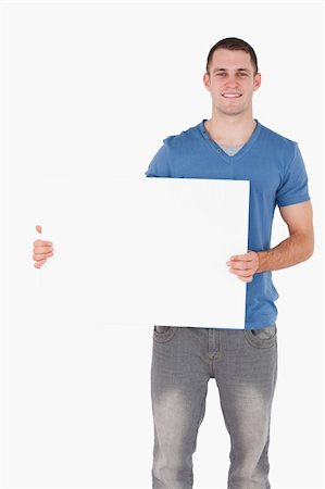 Portrait of a young man holding a blank panel against a white background Stock Photo - Budget Royalty-Free & Subscription, Code: 400-05715307
