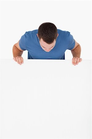 Portrait of a man looking at a blank panel against a white background Stock Photo - Budget Royalty-Free & Subscription, Code: 400-05715311