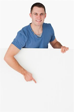 Portrait of a smiling man pointing at a blank panel against a white background Stock Photo - Budget Royalty-Free & Subscription, Code: 400-05715313