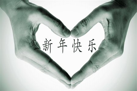 hands forming a heart and the sentence happy new year in chinese Stock Photo - Budget Royalty-Free & Subscription, Code: 400-05717707