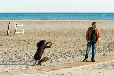 Woman taking photographs of a teenager on the beach Stock Photo - Budget Royalty-Free & Subscription, Code: 400-05730553