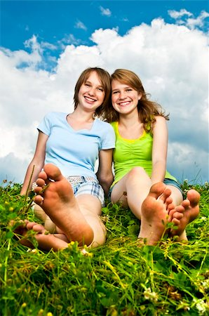Two young teenage girl friends sitting barefoot on summer meadow Stock Photo - Budget Royalty-Free & Subscription, Code: 400-05731721