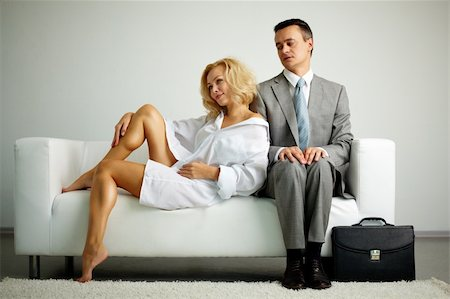 pressmaster - Photo of man in suit sitting on sofa and looking at seductive woman near by Stock Photo - Budget Royalty-Free & Subscription, Code: 400-05733826