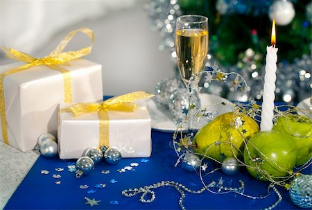 simsearch:400-05749231,k - Image of holiday table with flute of champagne, fruits, gifts, burning candle and decorations on it Stock Photo - Budget Royalty-Free & Subscription, Code: 400-05749222