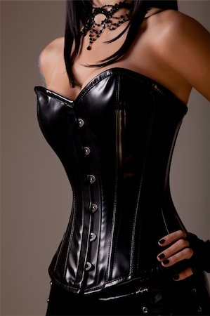 Slim sexy woman with hourglass figure in black leather corset, studio shot Stock Photo - Budget Royalty-Free & Subscription, Code: 400-05741379