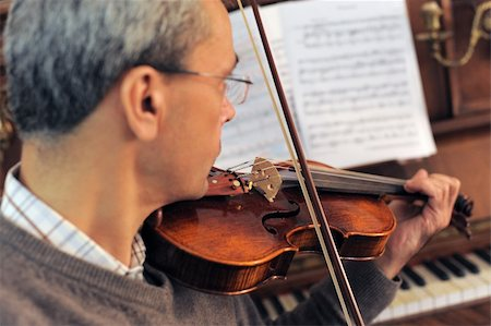 sheet music background - violinist with piano in the background, focus on the violin Stock Photo - Budget Royalty-Free & Subscription, Code: 400-05741621