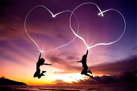 young couple jumping and drawing connected hearts by flashlight in the air on the beach before sunrise Stock Photo - Budget Royalty-Free & Subscription, Code: 400-05754197