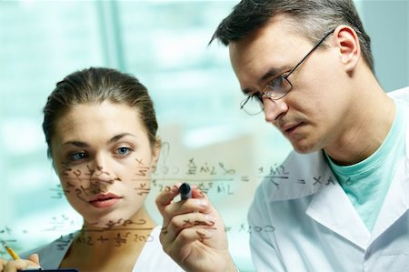pressmaster - Serious scientist explaining chemical formula to his co-worker Stock Photo - Budget Royalty-Free & Subscription, Code: 400-05750057