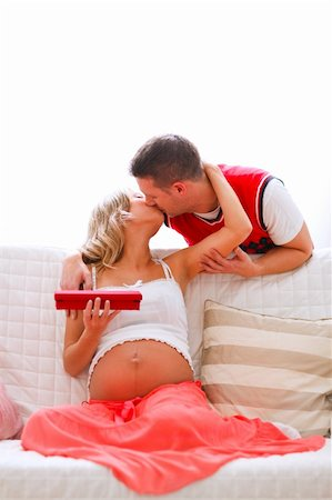 Young pregnant woman kissing her husband who present her jewelery Stock Photo - Budget Royalty-Free & Subscription, Code: 400-05750813