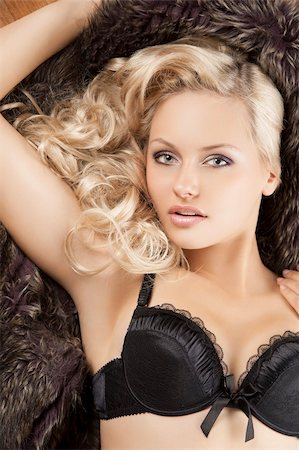 close up portrait of young beautiful girl with blond curly hair wearing a black bra laying on fur Stock Photo - Budget Royalty-Free & Subscription, Code: 400-05752037