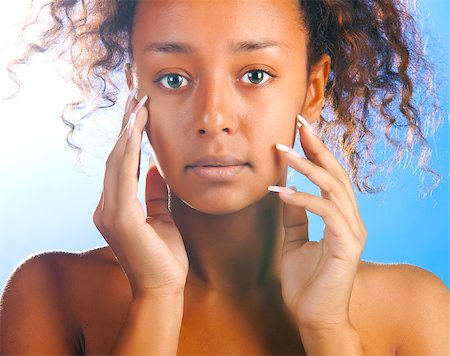 sunny beautiful mulatto woman with is touching her face and looking at camera on sky background Stock Photo - Budget Royalty-Free & Subscription, Code: 400-05875578