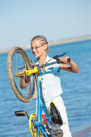 beautiful young girl standing with her bicycle. the background sea Stock Photo - Budget Royalty-Free & Subscription, Code: 400-05875947
