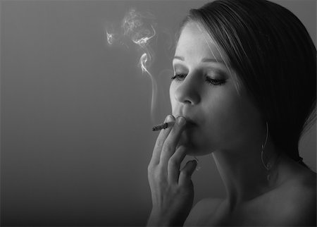 beautiful young woman smoking a cigarette in the dark Stock Photo - Budget Royalty-Free & Subscription, Code: 400-05889217