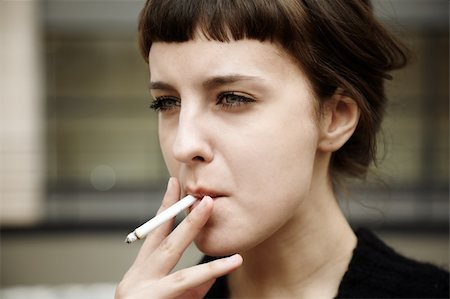 real young woman smokes on the street, selective focus Stock Photo - Budget Royalty-Free & Subscription, Code: 400-05880837