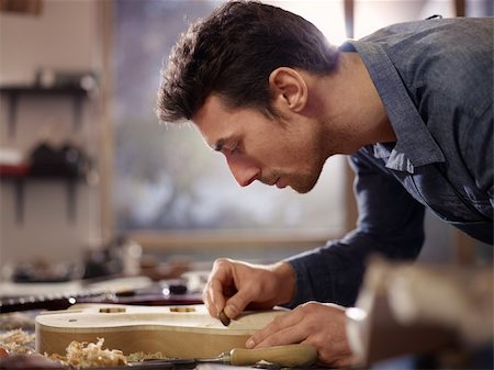 diego_cervo (artist) - mid adult man at work as craftsman in italian workshop with guitars and musical instruments, smoothing guitar body Stock Photo - Budget Royalty-Free & Subscription, Code: 400-05881014