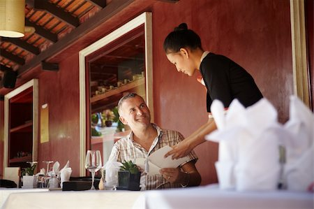 diego_cervo (artist) - Attractive young asian woman working as waitress in exclusive restaurant and attending customer with menu Stock Photo - Budget Royalty-Free & Subscription, Code: 400-05881021