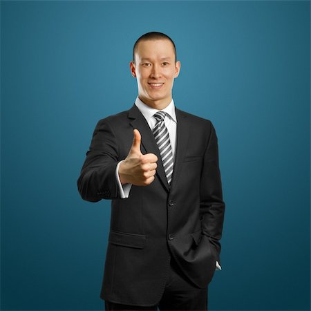 asian businessman in black suit shows well done against different backgrounds Stock Photo - Budget Royalty-Free & Subscription, Code: 400-05881625