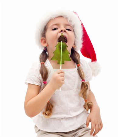 red stick candy - Little girl busy licking a christmas tree shaped candy - isolated Stock Photo - Budget Royalty-Free & Subscription, Code: 400-05882496