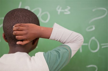 Schoolboy thinking with his hand on his head in front of a blackboard Stock Photo - Budget Royalty-Free & Subscription, Code: 400-05895212